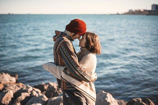 Un homme grand regarde une femme rousse plus petite. Il sourit elle le regarde avec amour. Ils se regardent tous les deux dans les yeux. Ils s'aiment. Ils sont devant la mer. Ils se trouvent en Irlande.